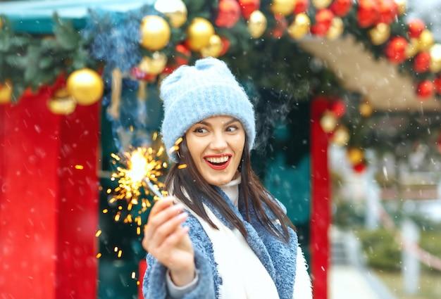 Возбужденная молодая женщина в синем пальто наслаждается отпуском с бенгальскими огнями во время снегопада