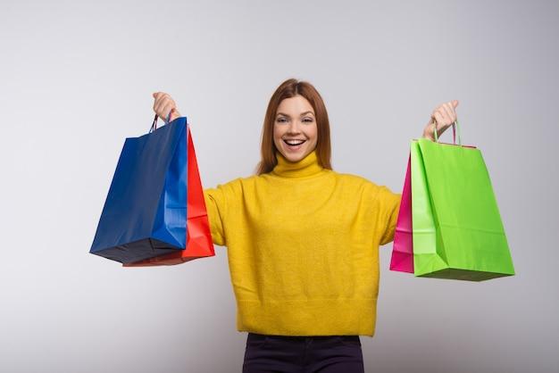 Взволнованная молодая женщина с красочными сумками