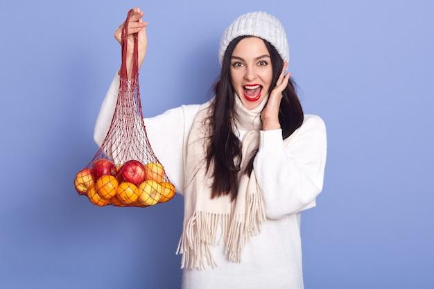 新鮮な熟したマンダリンを持つ興奮した若い女性
