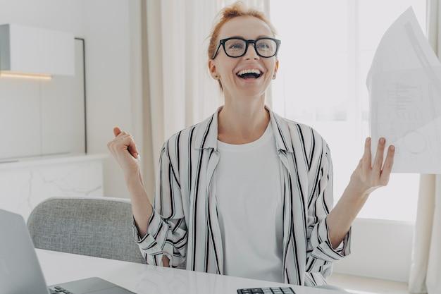 紙幣を手にした興奮した若い女性がついに自宅で住宅ローンの借金を返済