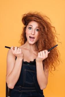 オレンジ色に孤立して立っている間、目の鉛筆を保持している赤い髪の興奮した若い女性