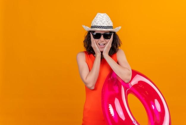 Una giovane donna eccitata con i capelli corti in una camicia arancione che porta cappello da sole e occhiali da sole che tengono anello gonfiabile