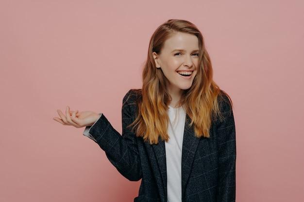 어두운 정장 재킷에 밝은 분홍색 배경에 서있는 어깨를 으쓱하는 손을 기울이는 흥분된 젊은 여성, 물결 모양의 생강 중간 길이의 머리카락이 웃고있는 귀여운 소녀
