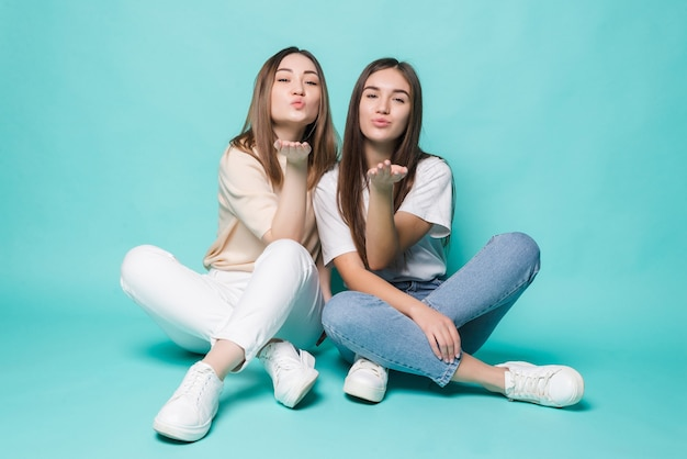 Excited young women blow kiss posing on the floor isolated on turquoise wall.