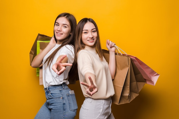 Excited young women girls friends hold package bag with purchases after shopping posing isolated on yellow wall . people lifestyle concept.