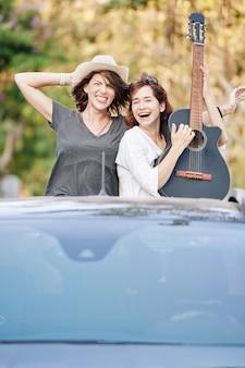 車のトランクに乗って興奮した若い女性