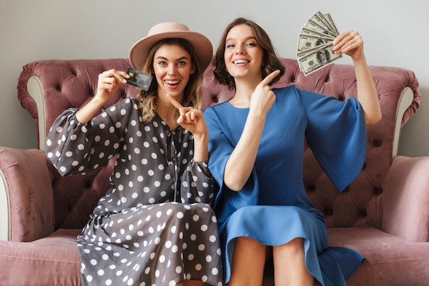 Excited young women shopaholics holding money and credit card.