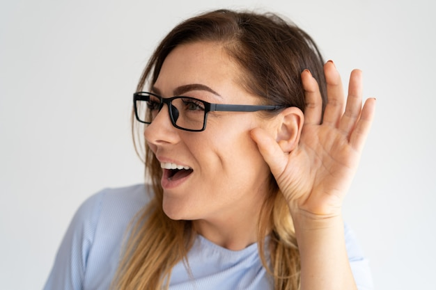 Excited милая женщина держа руку около уха