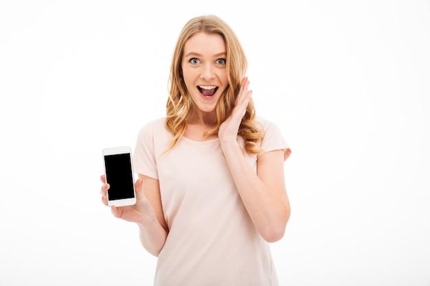 Excited молодая женщина показывая дисплей мобильного телефона.