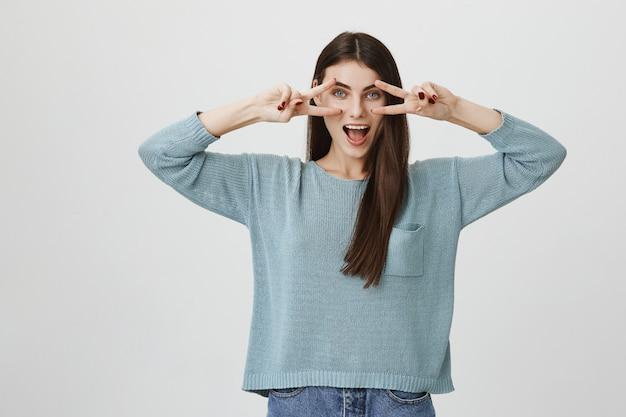 Excited счастливая женщина показывая знаки мира над глазами