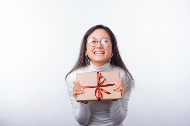 Excited молодая женщина показывает обернутый подарок пока усмехающся на камере.