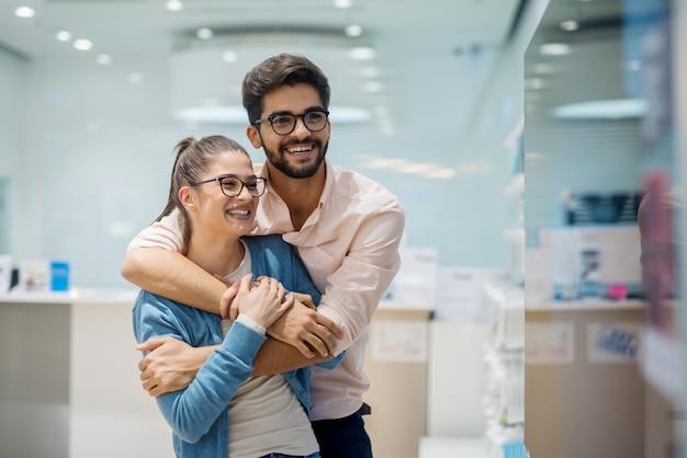Закройте вверх по взгляду портрета милых excited очаровательных молодых пар студента в влюбленности обнимая и смотря большое новое тв в техническом магазине.