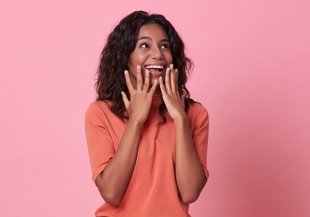 Excited красивое африканское счастье женщины нося вскользь оранжевую футболку на пинке.