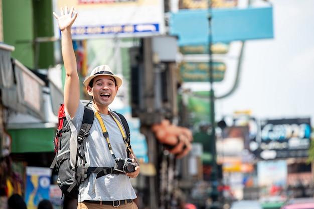 Excited азиатский туристский человек поднимая руку для приветствия кто-то