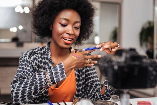 興奮。新しい明るい色見本を試している間、興味を示している美しい浅黒い肌の女性