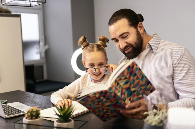 興奮。本の中の絵を見ながら興奮している白いセーターを着たかわいい長髪の女の子