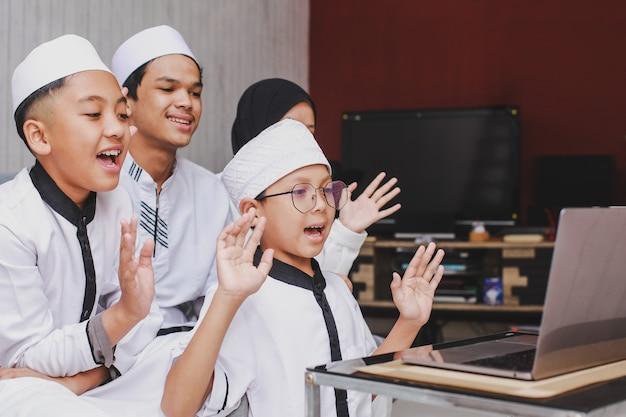 Eid mubarak 축하 행사 기간 동안 비디오 대화를하고 노트북 앞에서 즐거운 시간을 보내는 신나는 이슬람 가족