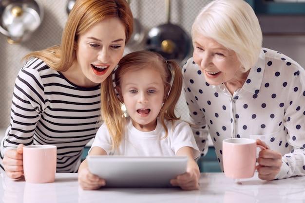 エキサイティングな漫画。どんでん返しに面白がって見ながらピンクのマグカップからコーヒーを飲む彼女の祖母と母親と一緒にタブレットで漫画を見ている楽しい女の子