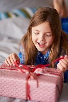 クリスマスプレゼントを開くエキサイティングな女の子