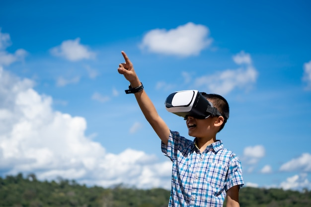 Exciting kids watching virtual reality box or vr box on hills nature background
