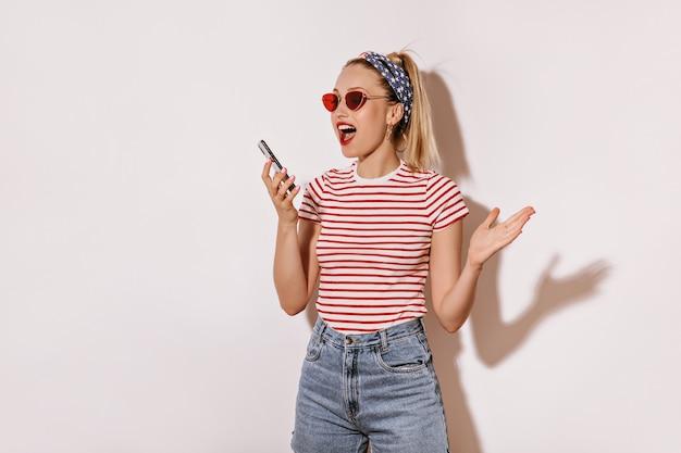 ヘッドバンド、赤いサングラス、縞模様のtシャツ、隔離された壁に電話を保持しているデニムのブロンドの髪を持つエキサイティングな女性