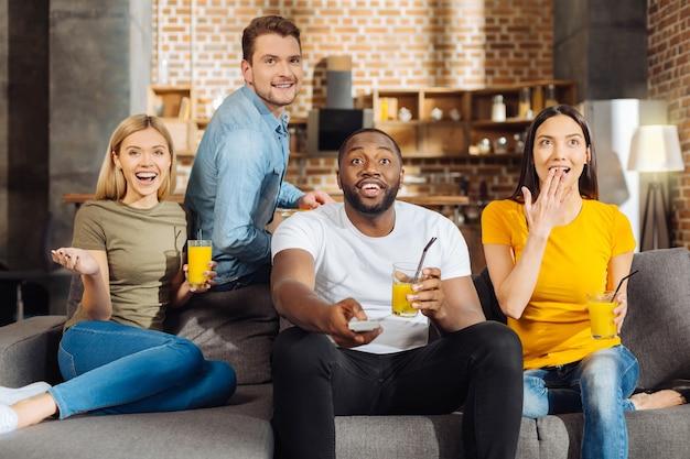 Увлекательный фильм. четверо изумленных, шокированных и позитивных друзей сидят на диване, пьют сок и проводят время вместе