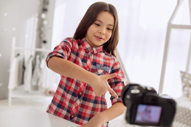Увлекательная история. очаровательная девочка подросткового возраста в клетчатой рубашке рассказывает забавную историю своим зрителям и эмоционально жестикулирует во время записи видеоблога.