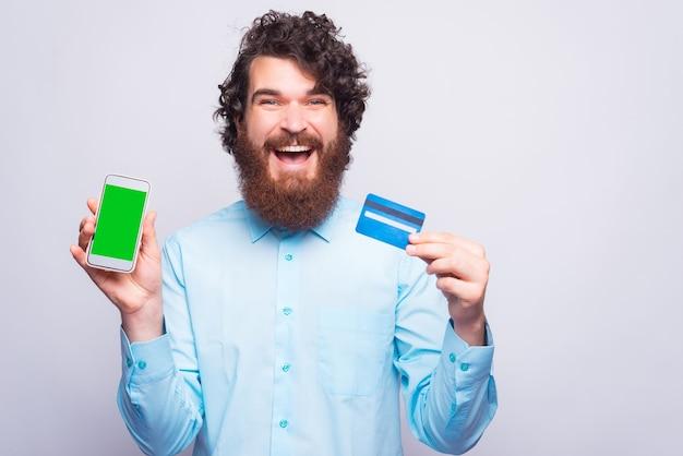 クレジットカードとカメラを見ている電話を持っているエキサイティングな若い男