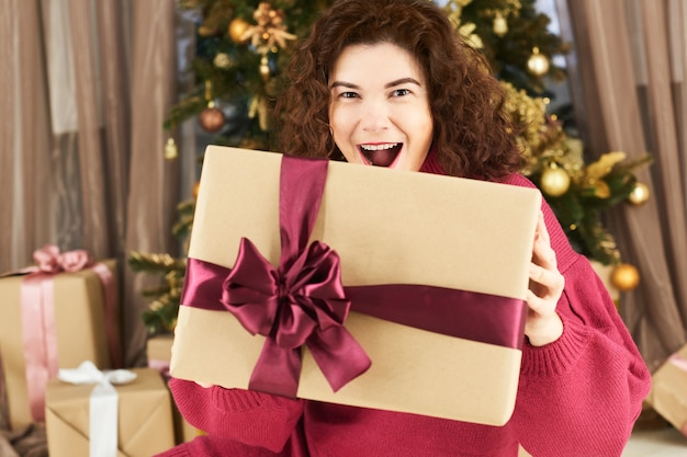 Захватывающая молодая женщина, держащая рождественскую подарочную коробку