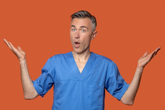 Exclamation, gesture. good looking caucasian male in doctors suit showing exclamation and surprise gesture on orange background