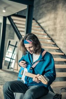 唯一無二の才能。スタイリッシュなアパートで電子ギターを弾きながら、幸せそうな笑顔の長い髪の男