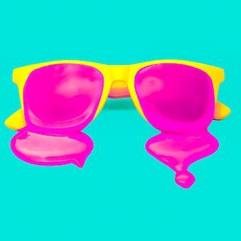 青い背景に排他的な黄色のヒップスターサングラス。ピンクのペンキが滴り落ちる。爆発の夏の色