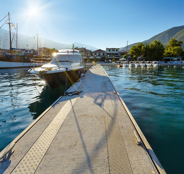 Экскурсионные корабли в бухте. туманный солнечный летний пейзаж побережья лефкады (нидри, греция, ионическое море).