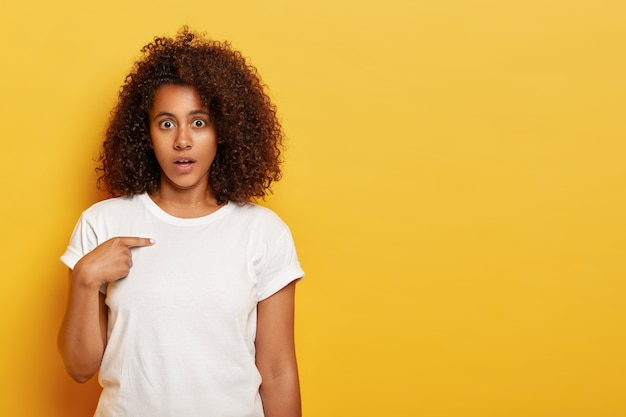 すみません?憤慨しているアフリカ系アメリカ人の女性は困惑していると感じ、自分を指さし、不快な言葉に驚いて、混乱しているように見え、白い服を着て、黄色い壁に立ち向かい、空白を脇に置きます