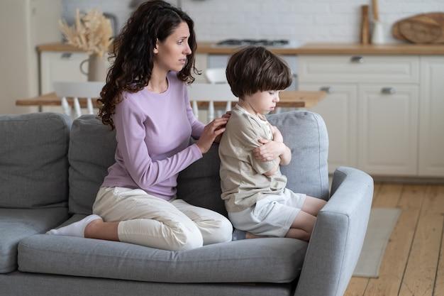 言い訳をする母親は、思いやりのあるお母さんを眉をひそめ、無視して頑固な気分を害した男の子の子供と和解しようとします