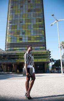 Исполнительная черная женщина в деловом районе в городе под голубым небом