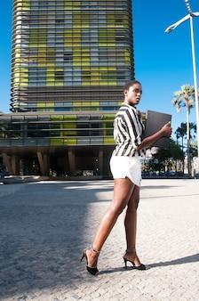 Исполнительная черная женщина в деловом районе города под голубым небом