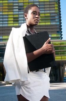 Исполнительная черная женщина в деловом районе в городе под синим
