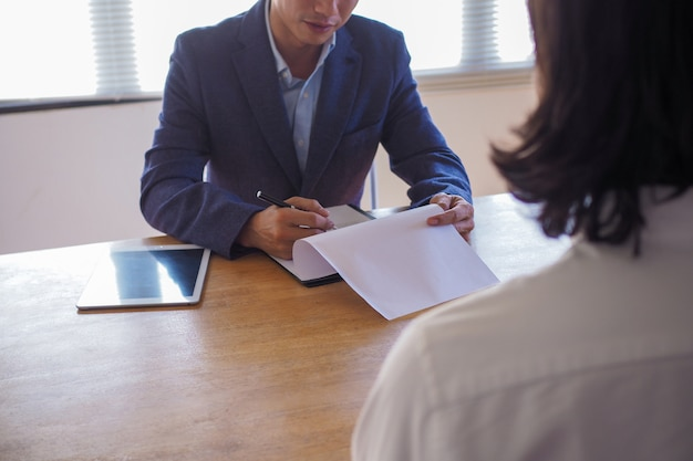Executive boss interviewing candidate and holding a tablet