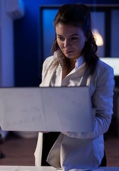 재무 보고서 작업을 하는 비즈니스 사무실에서 늦은 밤 노트북에 타이핑하는 경영진