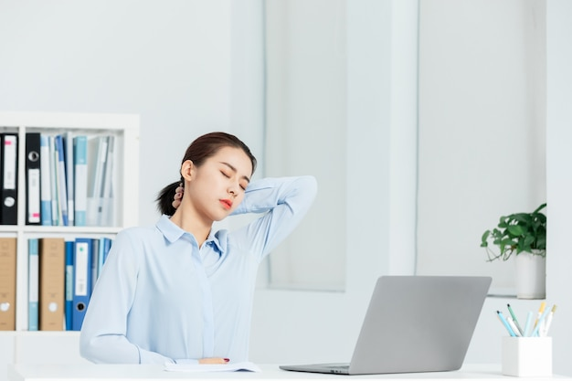 Executive business woman shoulder pain in an office
