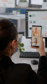 Executive business woman wearing protective face mask using phone for online videocall conference