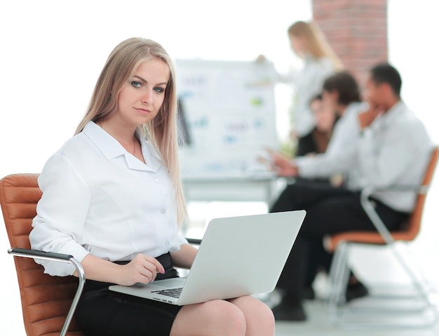 Executive business woman with a laptop on blurred background office.