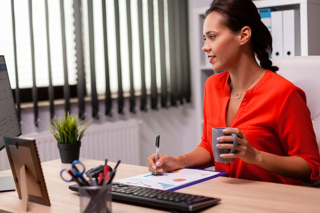 Executive businesswoman entrepreneur writing financial sales report looking at screen wearing red. successful financial auditor in data marteking looking at graphs on computer screen and writing repor