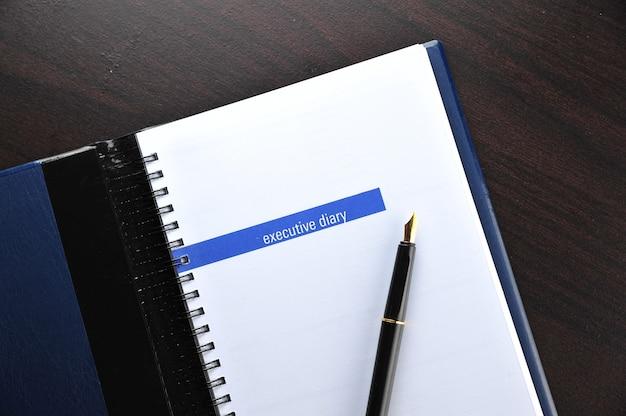 Исполнительный дневник с перьевой ручкой на деревянном столе