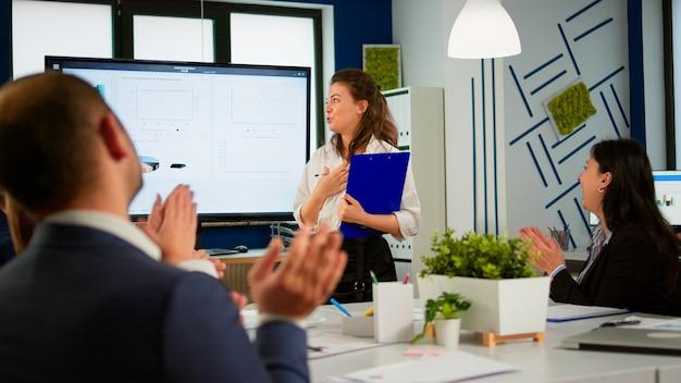 회사 전략을 발표하는 전무이사, 여성 관리자에게 박수를 보내는 비즈니스 청중, 디지털 차트 프레젠테이션에 대한 회의 세미나, 다민족 사무실 사람들이 박수를 치는 것에 대해 감사합니다.