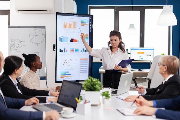 事務局長の女性ブリーフィングが会社の戦略を説明する同僚