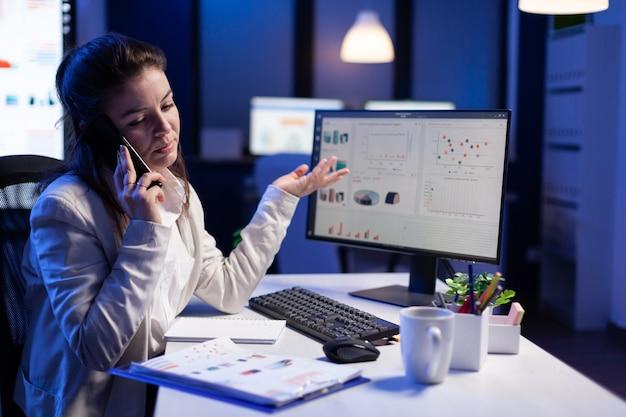 スマートフォンで従業員と話しているエグゼクティブ起業家は、営業所で新しいマーケティングコンセプトを作成します。夜遅くに机に座っている最新のテクノロジーネットワークを使用している忙しいマネージャー