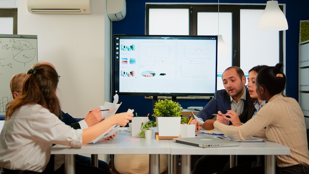 Executive explaining company's vision and potential to employees sitting at brainstorming table in broadroom with tv screen on the wall showing corporate growth