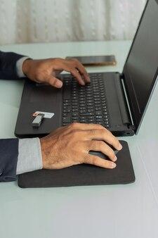 コンピューターで探して入力するエグゼクティブの男性